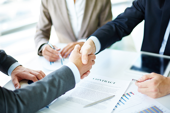 Business partners handshaking over business objects on workplace